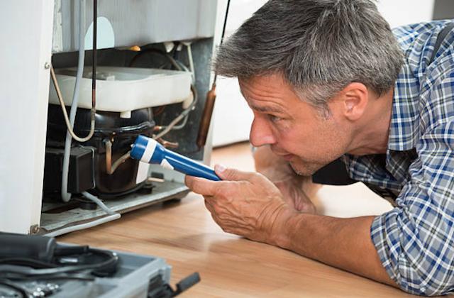 repairman under refrigerator